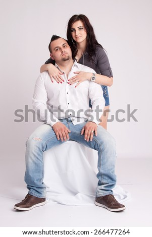 Young woman rests behind the seated young man - stock photo