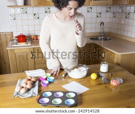 Young woman reviewing the ingredients of a recipe for cupcakes. Woman checking ingredients and cooking utensils before making homemade cupcakes  - stock photo