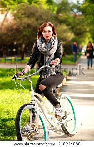 Young woman riding a bicycle in the green city park - stock photo
