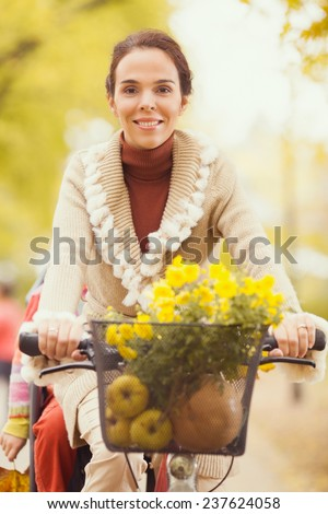 Young woman riding a bicycle with a child sitting on a rear bike rack - stock photo