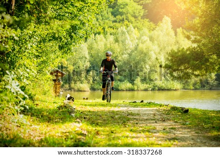 Young woman riding a bike in the forest next to a lake at sunset. - stock photo