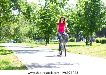 Young woman riding a bike in the park. - stock photo