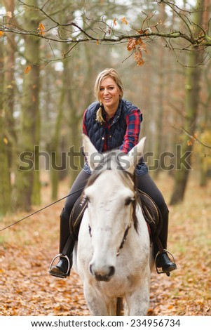 Young woman riding a horse - stock photo