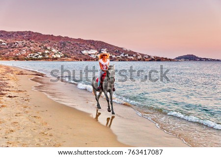 Young woman riding a horse at sunset on the beach of Plaka in Naxos island, Greece