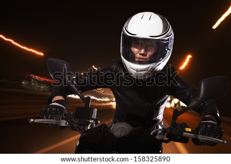 Young woman riding a motorcycle through the streets  - stock photo
