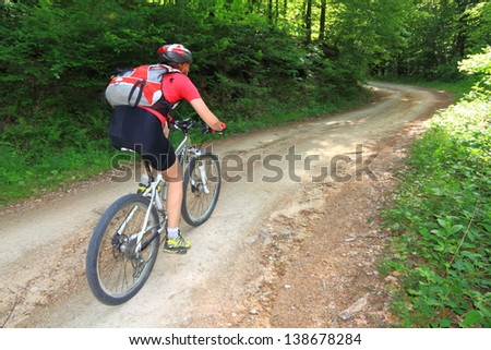 Young woman riding a mountain bike on a gravel road through the woods - stock photo