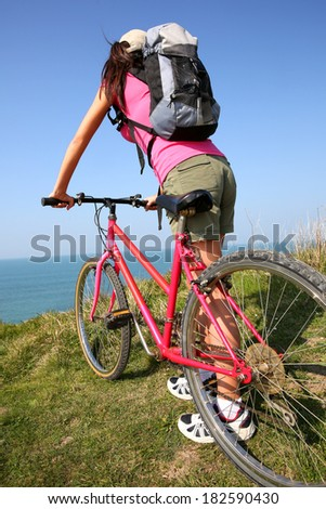 Young woman riding bike by ocean coast