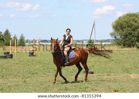 Young woman riding chestnut horse - stock photo
