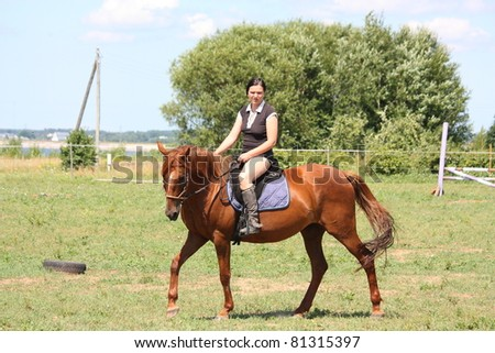Young woman riding chestnut horse