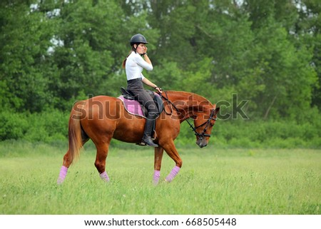 Young woman riding horse through forest