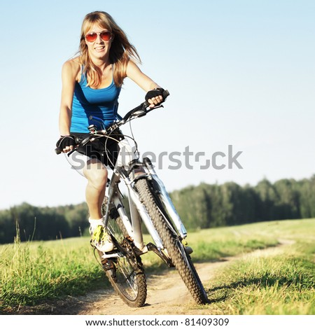 Young woman riding on a bicycle on a countryside road - stock photo