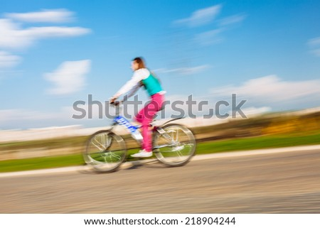 Young woman riding on blue bicycle in park