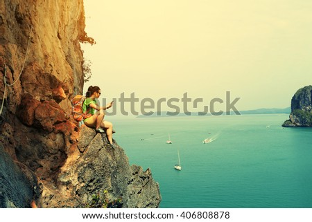 young woman rock climber use smartphone at seaside mountain cliff - stock photo