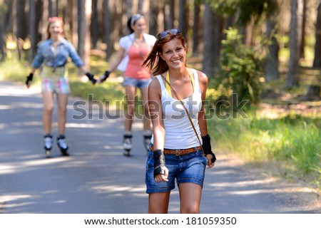 Young woman roller skating outdoors with friends summer sport - stock photo