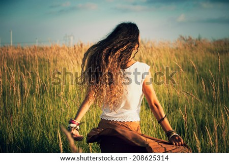 young woman run in summer field of grass retro colors back shot - stock photo
