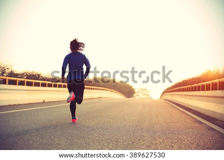 young woman runner athlete running at road - stock photo