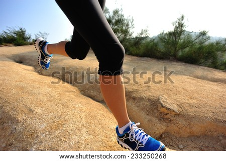 young woman runner legs running on mountain trail  - stock photo