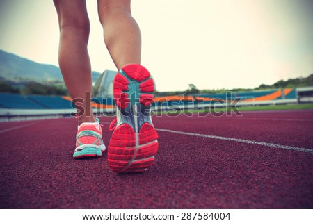 young woman runner legs running on track,vintage effect