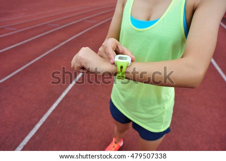 young woman runner ready to run set and looking at sports smart watch