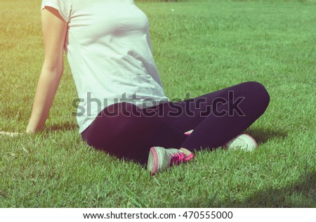 Young woman runner resting after workout session on sunny morning