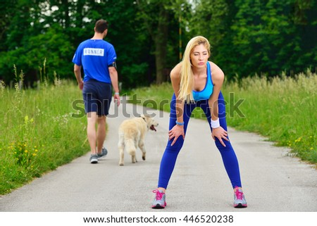Young woman runner resting after workout session on sunny morning. Female fitness model sitting on street along pond in city. Female jogger taking a break from running workout. - stock photo