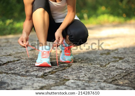 young woman runner tying shoelaces on stone trail - stock photo