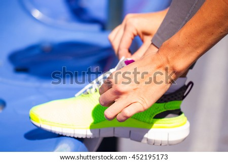 Young woman runner tying shoelaces, summer sport. Outdoor. Close Up
