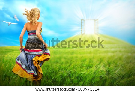 Young woman running across beautiful field to the bright luminous door on a hill. Bright future affection concept - stock photo