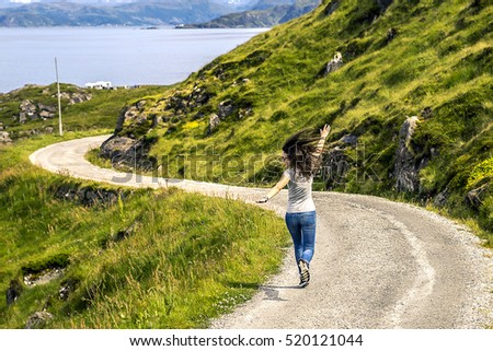 Young woman running along the countryside road, Norway