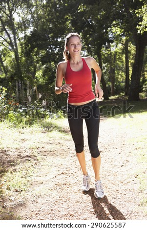 Young Woman Running Along Woodland Path