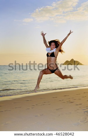 young woman running and jumping on the beach in hawaii
