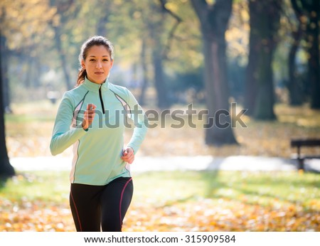 Young woman running and training in autumn nature - stock photo