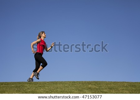 young woman running at the top of a hill