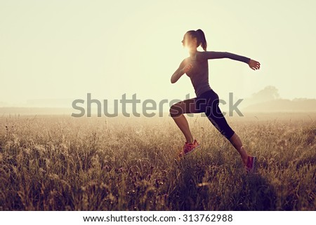 Young woman running during sunset