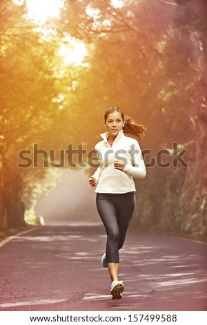 Young woman running. Female runner jogging on misty road with the early morning at sunrise with sun breaking through the trees as she trains during a fitness workout. - stock photo