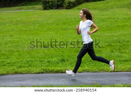 Young woman running in city park - stock photo