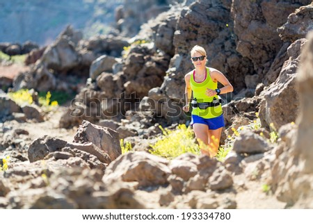 Young woman running in mountains on sunny summer day. Beauty female runner jogging and exercising outdoors in nature, rocky trail footpath on La Palma, Canary Islands - stock photo