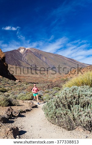 Young woman running in mountains on sunny summer day. Beauty female runner jogging and exercising outdoors in nature, trail running training on rocky trail footpath on Tenerife, Canary Islands