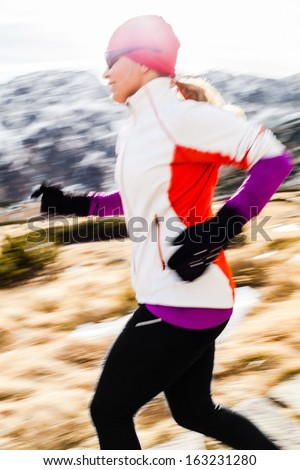 Young woman running in mountains on winter fall sunny day. Female runner exercising outdoors in nature, sunset. - stock photo