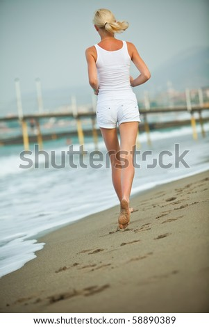 Young woman running in the beach