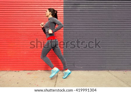 Young woman running in the city getting fit toned body urban environment copy space - stock photo