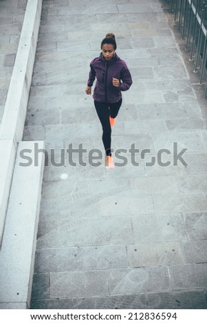 Young woman running in the city on river bank - stock photo