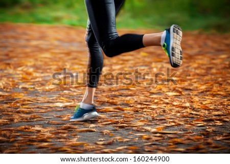 young woman running in the early evening autumn leaves