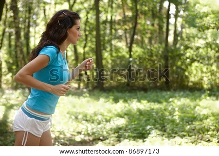 Young woman running in the park listening to music - stock photo