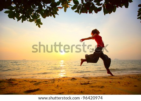 Young woman running on a beach at sunset - stock photo