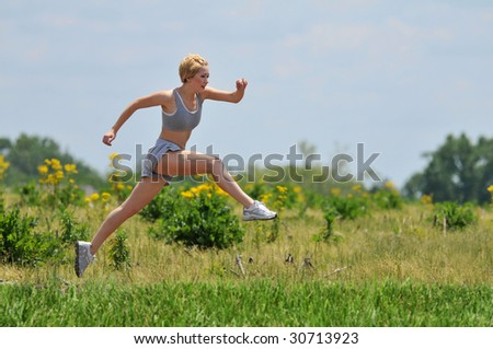Young woman running on a dirt road outdoors on a sunny day