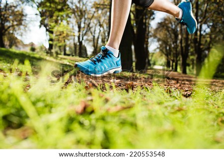 Young woman running on a road during day in the park in autumn. Selective focus. Low depth of field. Detail of sport feet on trail. - stock photo