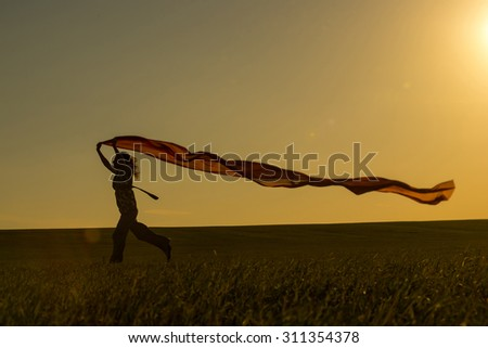 Young woman running on a rural road at sunset in summer field. Lifestyle freedom sports background. Happiness concept. - stock photo