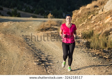 Young woman running on a rural road. Lifestyle sports background.