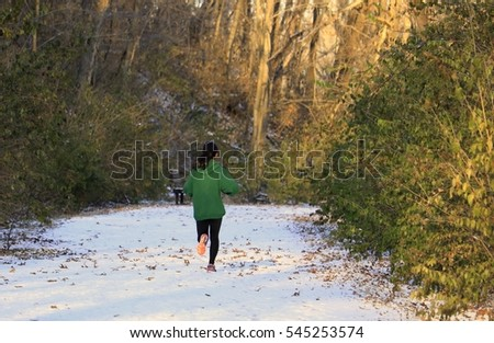 Young woman running on a snowy trail; winter in Missouri